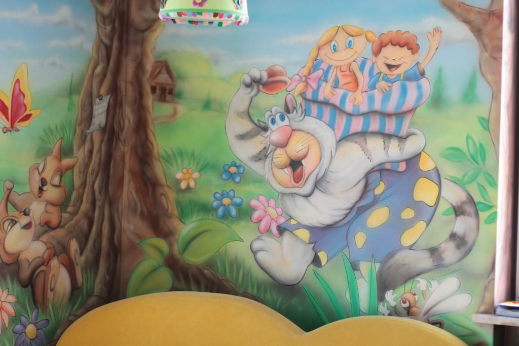 Malowanie grafitti na ścianie w dziecięcym salonie fryzjerskim
