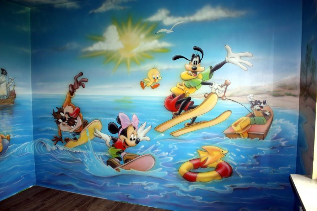 Malowanie kolorowych postaci z bajek na ścianie w pokoju dziecka,