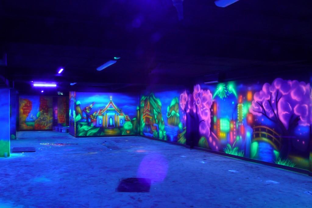 Swiecące grafitti na ścianie w kregielni, malowanie farbami UV,