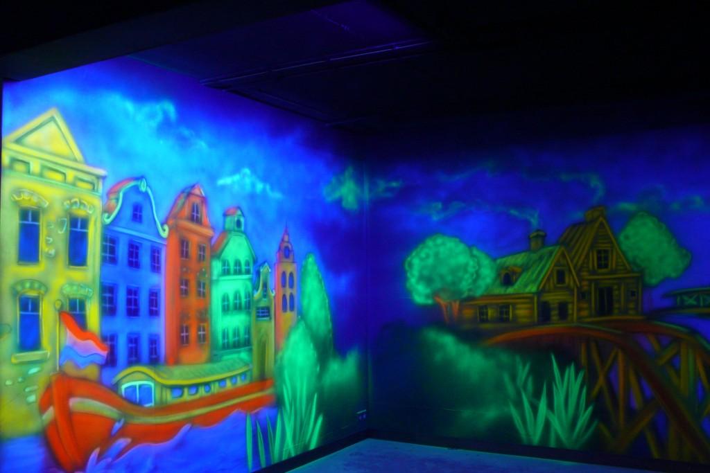 Malowanie grafitti na ścianie farbami UV, efekt luminescencji