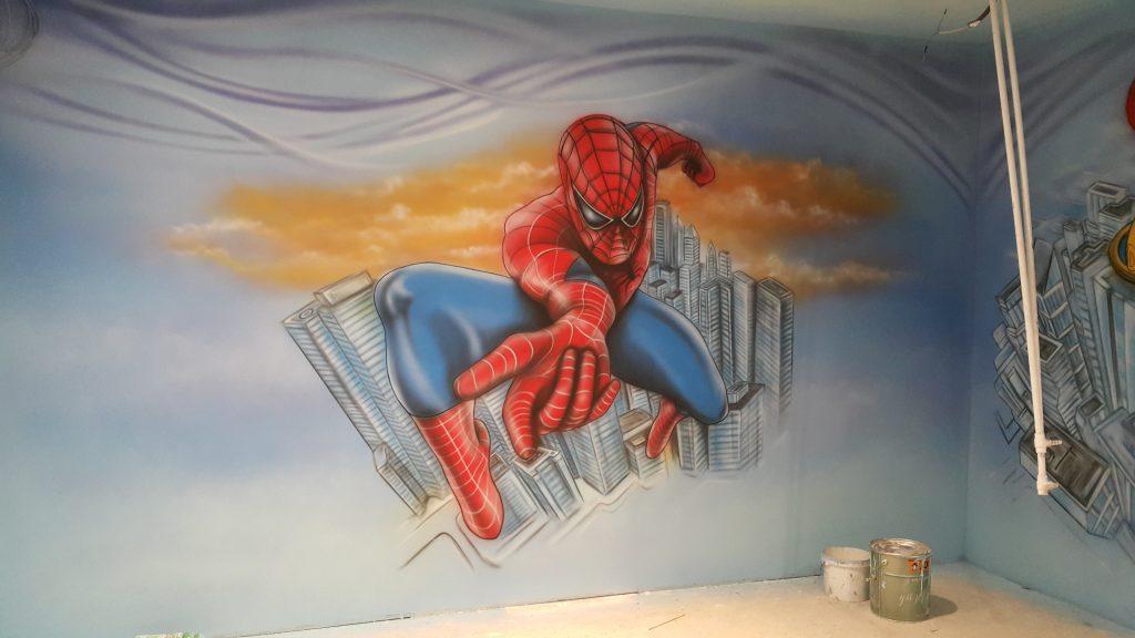 Malowanie ściany w bawialni, bajkowy motyw na ścianie