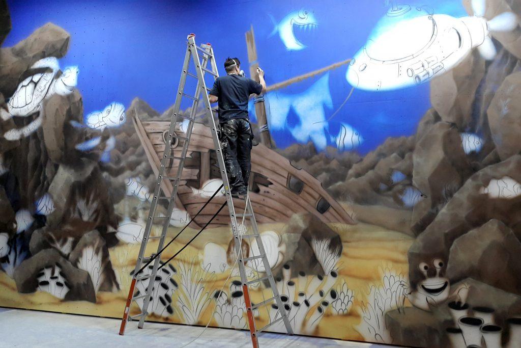 Malowanie graffiti na ścianie dla dzieci, mural w bawialni