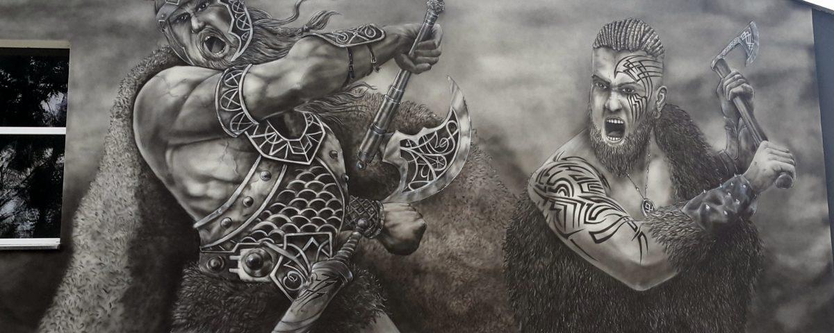 Czarno biały mural na elewacji budynku, wikingowie w boju