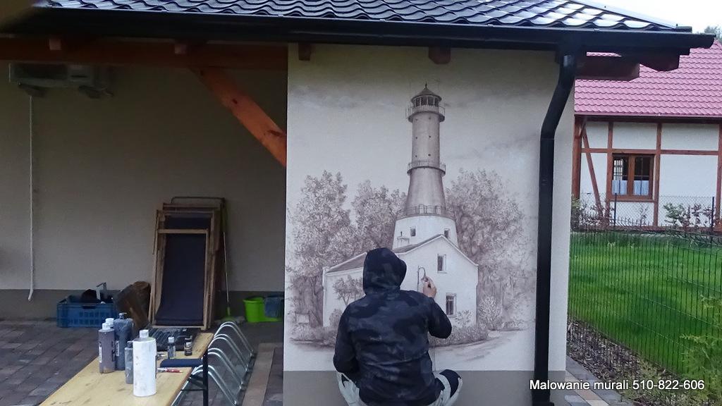 Malowanie latarni morskiej na scianie, aranzacja scian w domkach wczasowych