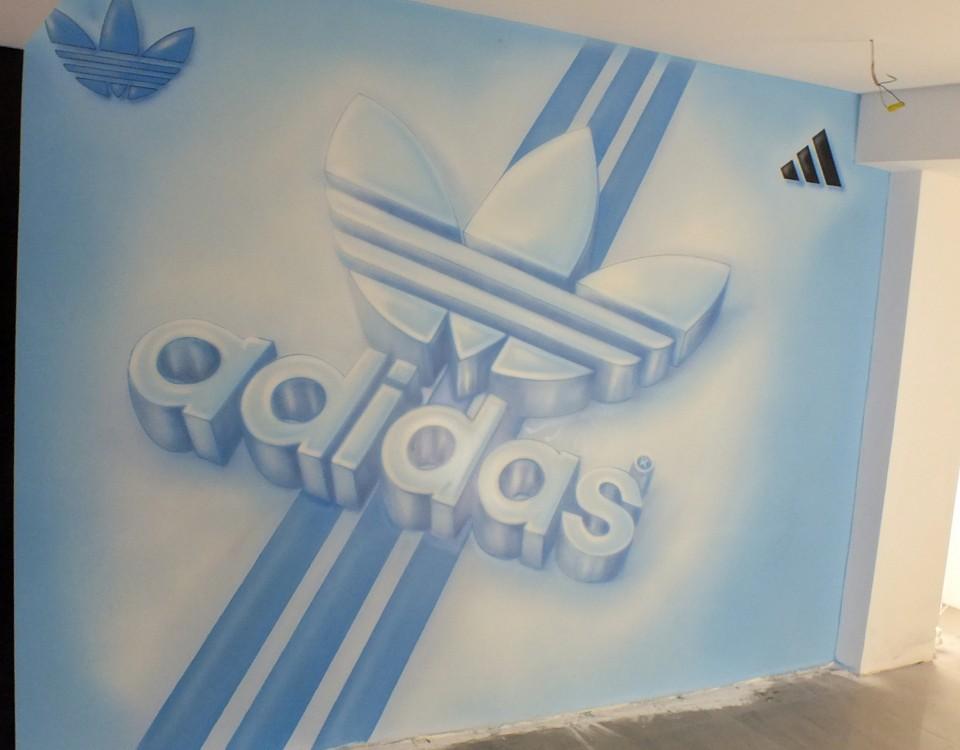 Malowanie loga na scianie w sklepie z butami, logotyp