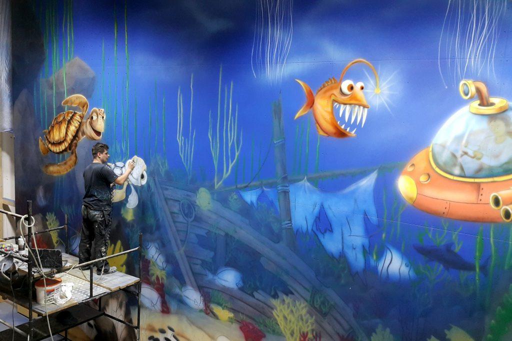 Graffiti dla dzieci, malowanie rybek na scianie w bawialni
