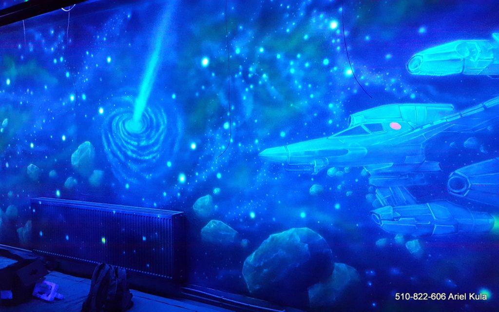 Malowanie kosmosu farbami UV w klubie, mural w ultrafiolecie, malowanie gwiazd i galaktyk