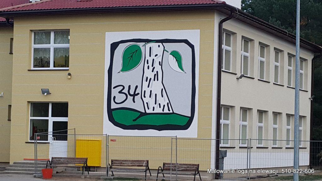 Malowanie loga na elewacji budynku szkolnego w Toruniu