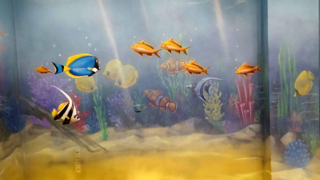 Wystrój przychodni w stylu rafy koralowej, malowanie ścian w przychodni w rybki, kolorowy mural w sali zabiegowej w szpitalu