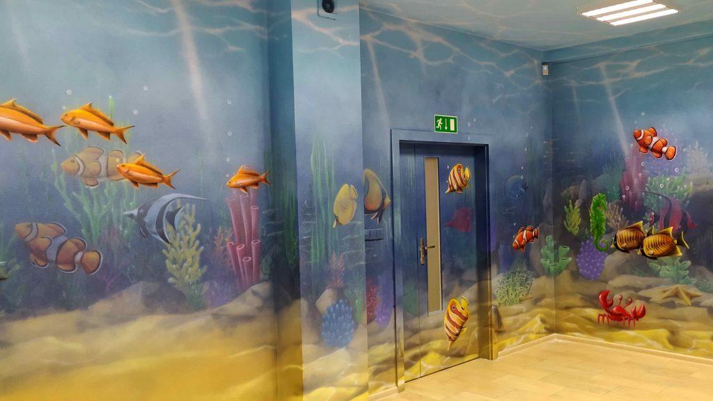 Malowanie ścian w przychodni w motyw głębi oceanu, nietypowa aranżacja dziecięcego gabinetu zabiegowego